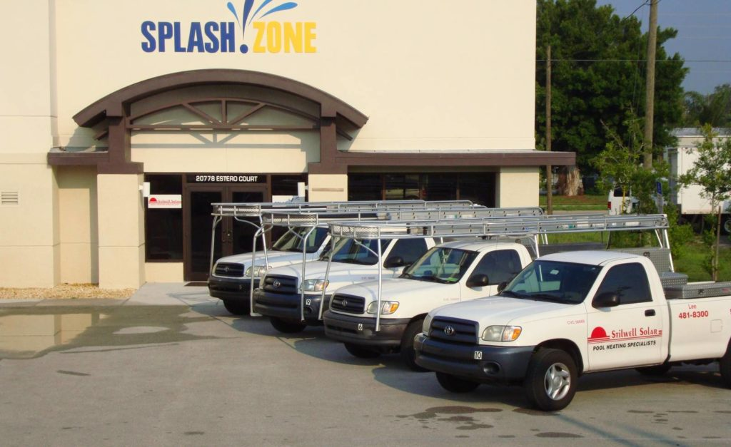 four of Stilwell Solar's service vehicles next to Splash Zone building