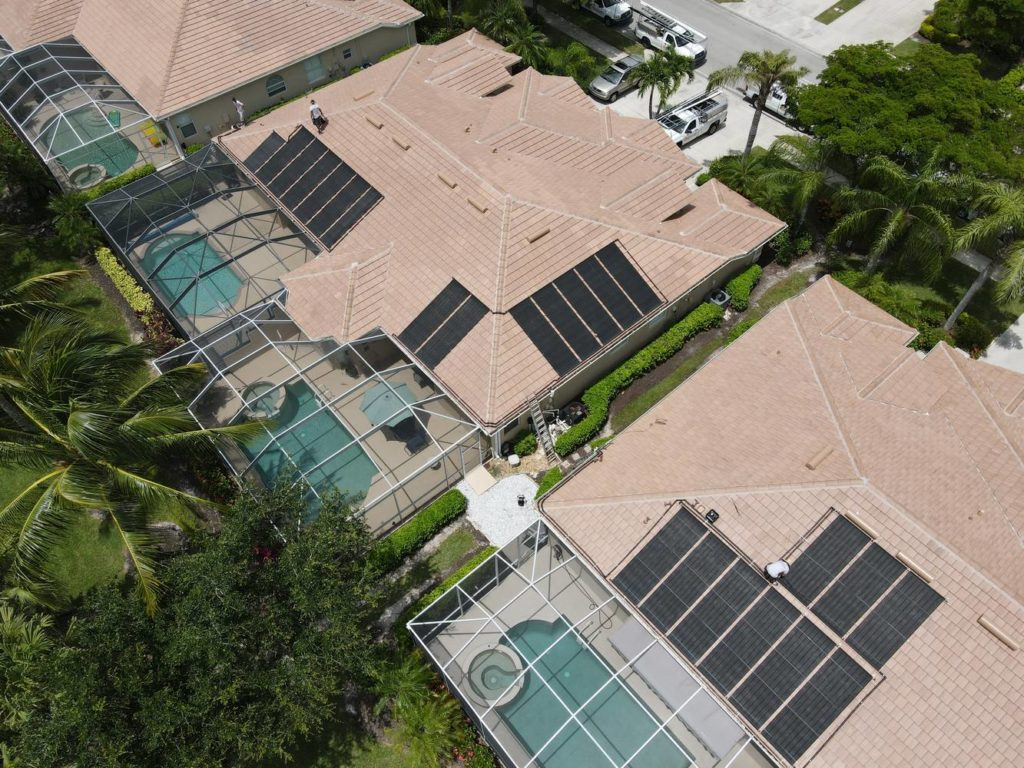aerial view of solar pool heating systems installed on two neighboring roofs
