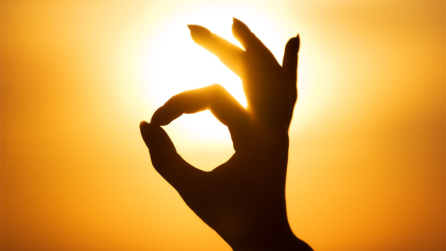 Hand making OK sign, circling the sun