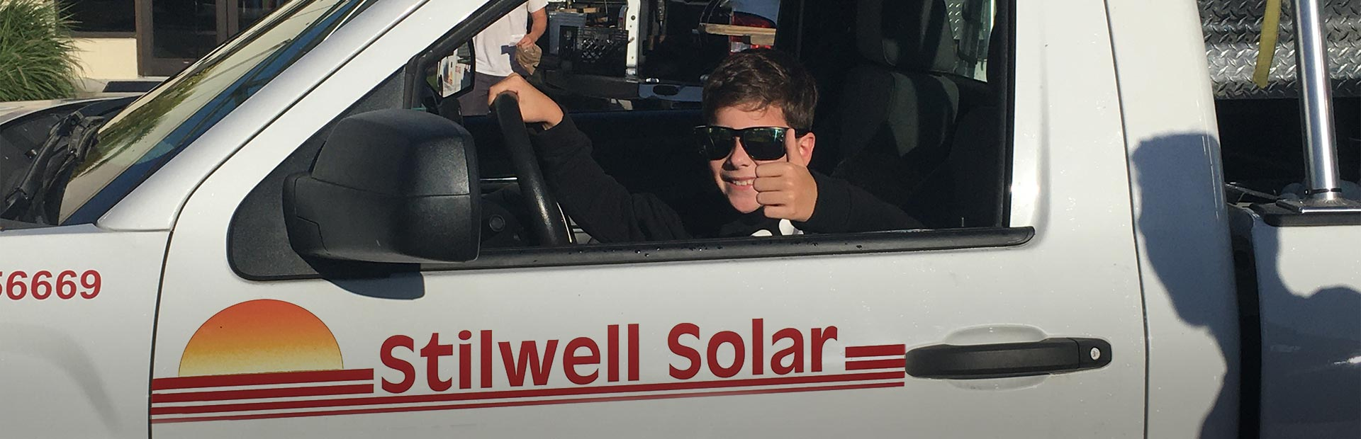 a next generation Stilwell Solar technician in truck giving a thumbs up