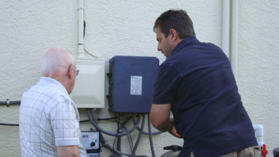 Stilwell employee showing old man part of a solar setup