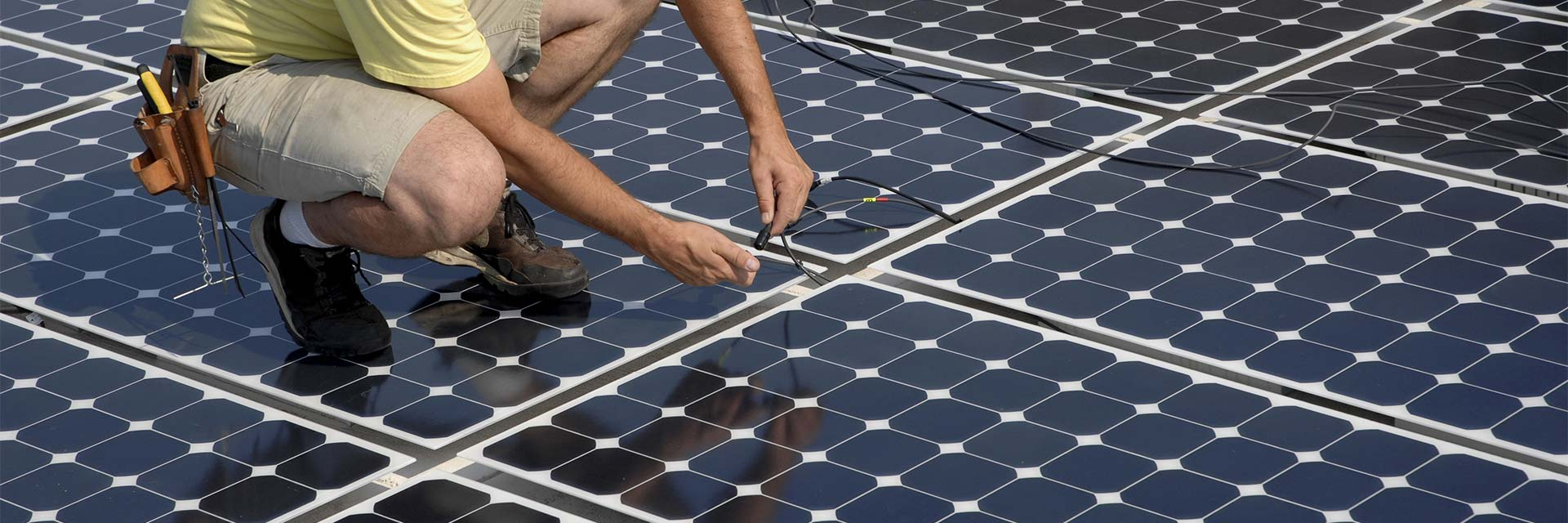 man installing solar electric panels